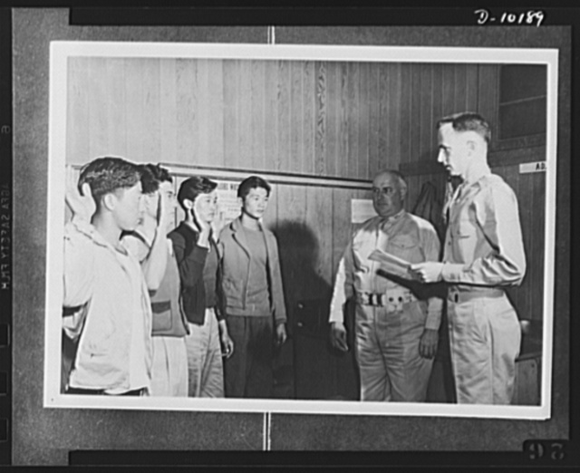 Japanese-American volunteers. Colonel James J. Doyle, second from right, commanding officer of Kauai, Hawaii Service Command looks on as the oath of induction is administered to the four young AJA [Americans of Japanese ancestry] volunteers of Kauai who went through the solemn pledge of allegiance immediately after Mitsuru Doi took his oath Thursday as the first man in the territory to be inducted. The oath is being administered by Major Charles V. McManus (extreme right), adjutant of the Service Command. The inductees are, from left to right: Goro Sadaoka, eighteen, of Lihue, who has two brothers on Oahu, both volunteers; Lenneth T. Tada, twenty-five, alumnus of the University of Hawaii, salesman for the Kauai Sales Company; Shigeo Suemori, twenty-one, of Lihue, whose brother Tadao was rejected after his physical examination, and Noboru Okamoto, eighteen, Lihue Plantation employee, who was born in Lihue and made a name for himself as pitcher for the Lihue baseball team