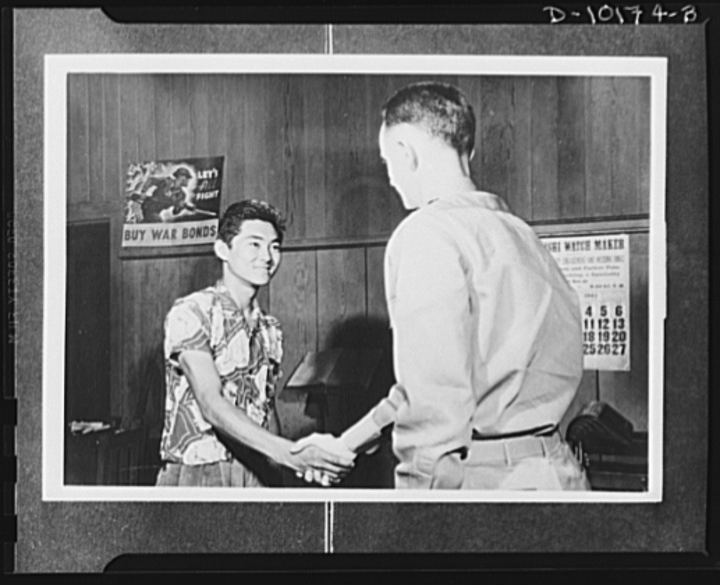 """Japanese-American volunteers. First of the territory's quota of 1,725 AJA (Americans of Japanese ancestry) volunteers to be inducted into the U.S. Army Combat Regiment now being formed, 18-year-old Mitsura Doi of Kauai, Hawaii, garage worker, receives congratulations from Major Charles V. McManus, adjutant of the Kauai Service Command who administered the oath of induction at 2:40 PM, Thursday, March 11. Doi was born at Koloa and volunteered with the blessing of his parents. """"I'm just waiting to begin training and get into action,"""" he said as he shook hands with Major McManus"""