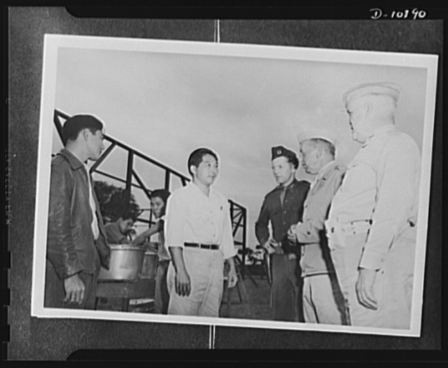 Japanese-American volunteers. Recognized among the AJA [Americans of Japanese ancestry] inductees by Major General Rapp Brush, commanding the Kauai District. Masato Sugihara, thirty-one, Kekaha school teacher, speaks with the general in the course of the latter's unexpected inspection of the provisional AJA camp. Sugihara, a married man, was the leader of the Makaweli board registrants from the time they assembled for their physical examination until their induction. Shown with the general are: Captain J. J. Fallon of the Service Command (left) and Colonel J.J. Doyle, commanding officer of the Service Command (right)