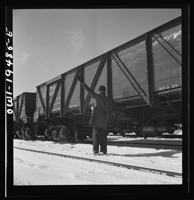 Joilet, Illinois. Conductor giving the brakeman the signal to apply and release the brakes before the train leaves on the Atchison, Topeka and Santa Fe