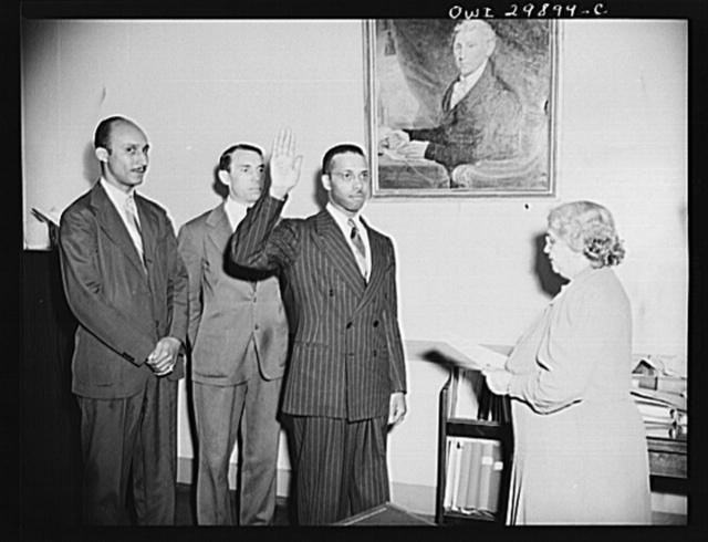 Joined Staff Of Attorney-General Biddle. The distinction of being the first Negro to become a member of the Trial Bureau of the Department of Justice goes to Martin A. Martin of Danville, Virginia who was sworn in on May 31, 1943. Photo shows Mrs. Nellie G. Plumley, Appointment Clerk, administering the oath. In the background is Attorney Oliver Hill of Richmond, Virginia, a friend of Mr. Martin and Frank Coleman, Special Assistant to Attorney-General Biddle. Mr. Martin also has the rank of Special Assistant