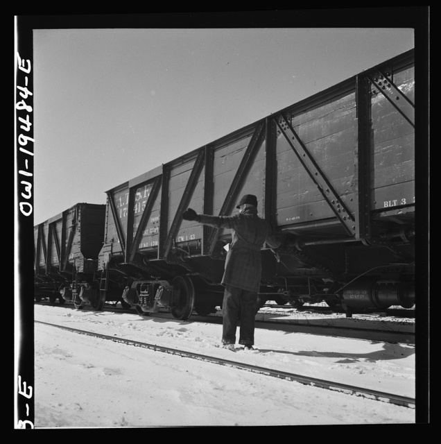 Joliet, Illinois. A conductor giving an engineer the signal to apply and release the brakes before the train leaves on the Atchison, Topeka, and Santa Fe Railroad between Chicago and Chillicothe, Illinois