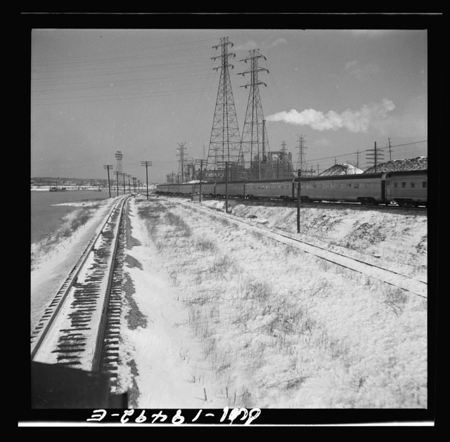 """Joliet (vicinity), Illinois. Passing the eastbound streamliner """"The Chief"""" of the Atchison, Topeka, and Santa Fe Railroad"""