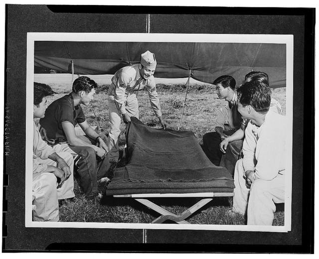 Kauai District, Territory of Hawaii. Sergeant Dewin Aguiar showing the AJA volunteers at the provisional camp how to make a bed