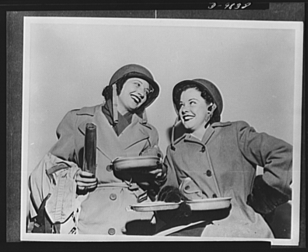 Kay Francis and Mitzi Mayfair, back from entertaining American troops in the British Isles and Africa, pose in the costumes they wore while traveling. They formed half a United Service Organization (USO) camp overseas unit, with Carole Landis and Martha Raye