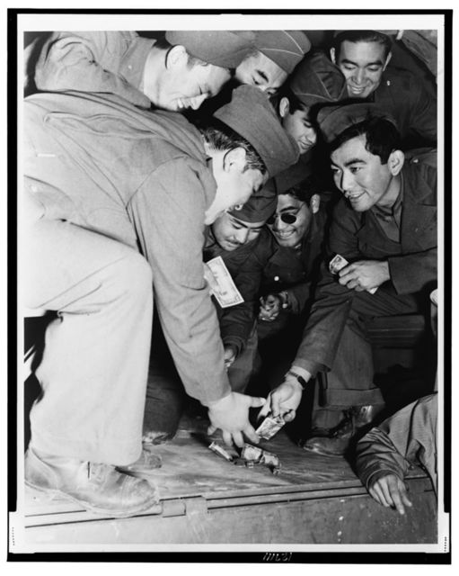 Killing time while the rest of their convoy loads, Japanese-American members of the 442nd Combat Team indulge in a little of the great American game of galloping dominoes with the bed of a GI truck as their table