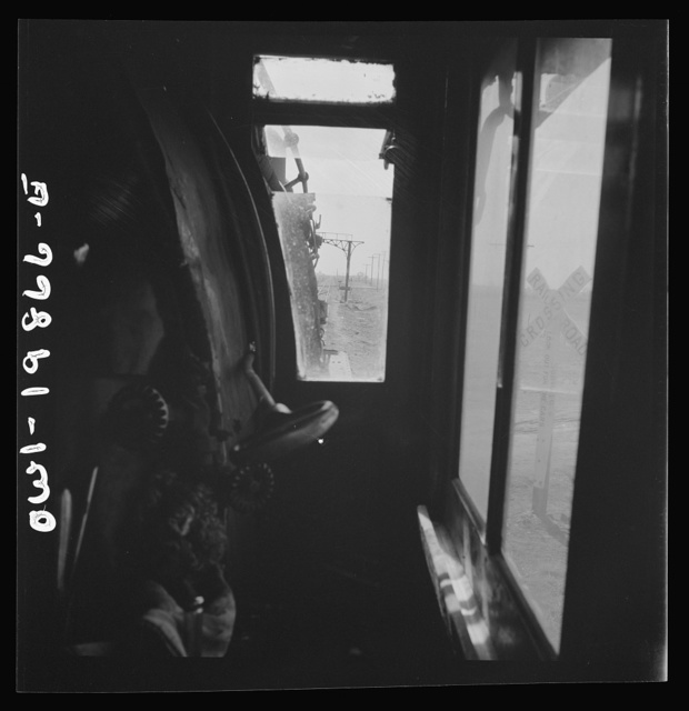 Kiowa, Kansas. The engineer's window in the cab of a locomotive. Waiting for block signal to change on the Atchison, Topeka, and Santa Fe Railroad between Wellington, Kansas and Waynoka, Oklahoma