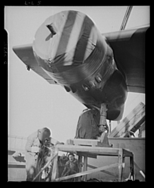 Lease lend loadings. Welding wheels of Douglas twin-engine light bombers to a platform on deck insures safe transit from an American port to the bombers' destination. Crews of highly specialized workers are required to load assembled planes on shipboard and to prevent their becoming dislodged in heavy seas. These precautions are unnecessary when planes are sent unassembled in crates; however, most planes going to the Near East are shipped ready for flight within one hour after docking, since in many ports competent unloading equipment is lacking or has been demolished by Axis raids