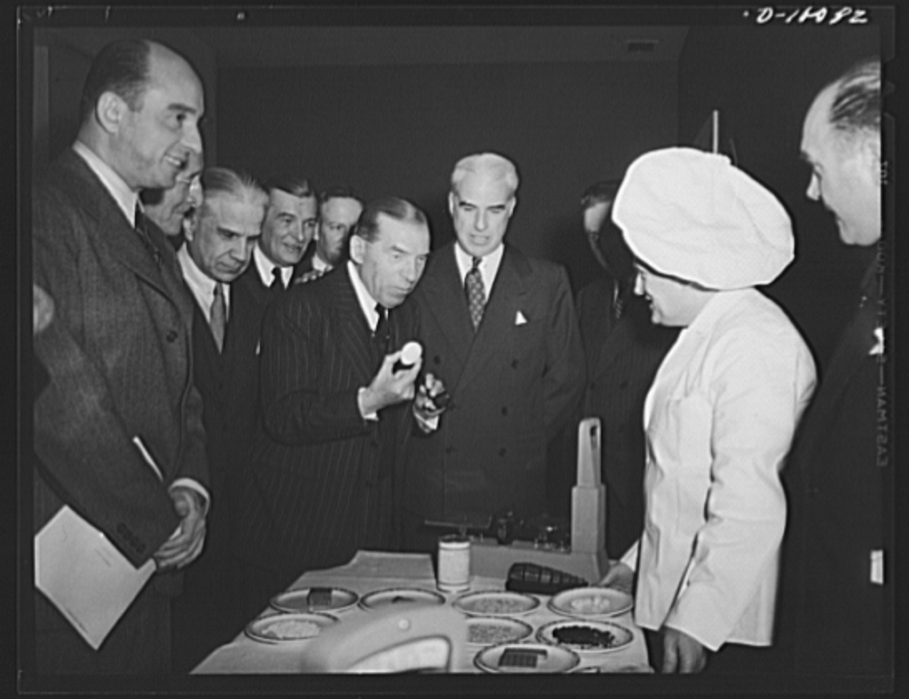 Lend-lease administrator Edward R. Stettinius, Jr., and guests at luncheon marking second anniversary of lend-lease, held March 11, 1943, at the Hotel Statler, Washington, D.C., look on as Representative Sol Bloom, chairman of the House Committee on Foreign Affairs, inspects an egg. Dehydrated food, later rehydrated, was served