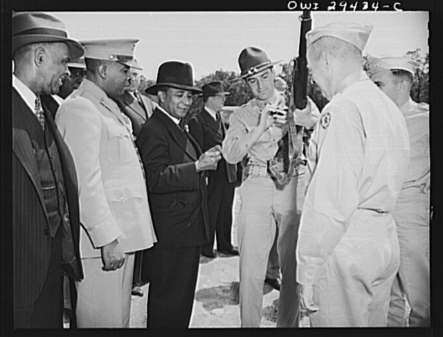 Liberian Presidential party visits Fort Belvoir. Two twenty-one gun salutes, a regimental review and a luncheon with the commanding officers were tendered His Excellency, Edwin Barclay, President of the Republic of Liberia, when he visited Fort Belvoir, Virginia, on May 29, 1943. An officer demonstrates the working of one of the United States Army's modern weapons for President Barclay as Walter F. Walker, Liberian Consul General, and Captain Alford Russ of the Liberian Frontier Forces, looks on.