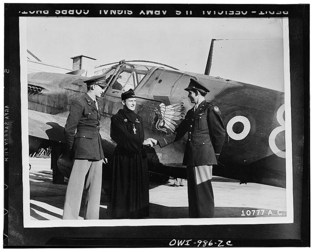 Lieutenant Hal C. Tunnell of Knoxville, Tennessee, left, introducing the Reverend R. P. Bougerol, Chaplain of the Lafayette Escadrille, to Lieutenant J. J. Ketcher of Fresno, California, full-blooded Cherokee Indian. The Indian head and Escadrille insignia are seen on the fuselage of the P-40