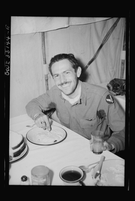 Lieutenant Richard E. Duffey, twenty-four, Walled Lake, Michigan, who accounted for five German Junker-52 transport planes over the Sicilian straits, eating on his return to 57th Fighter Group base somewhere in Tunisia