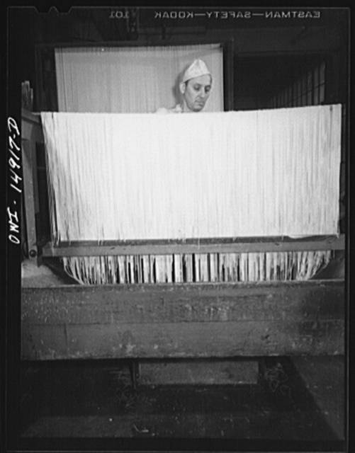 Long Island City, New York. Atlantic Macaroni Company, makers of Caruso brand products. Worker hanging out spaghetti to dry
