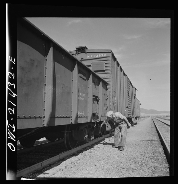 Ludlow, California. Conductor W.C. Scott inspecting his train on the Atchison, Topeka, and Santa Fe Railroad between Needles and Barstow, California