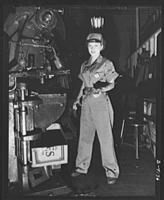 Madelon O'Leary operates a punch press in a well-cut, one-piece overall. Trim--and plenty of room for action. Visor-front cap completely covers hair for safety and essential neatness