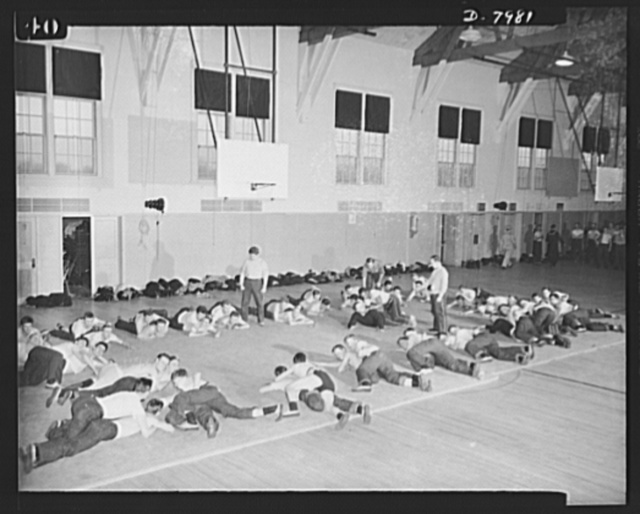 "Manhattan Beach Coast Guard training station. A modified form of ""commando"" tactics is part of the physical training course for enlistees at Manhattan Beach Coast Guard training station. Jim Walker, former Iowa University football star, is shown demonstrating wrestling holds to a gym class at Manhattan Beach"