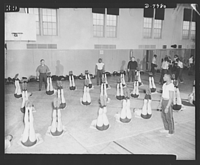Manhattan Beach Coast Guard training station. Eulance Peacock, member of the 1930 American Olympic Team and co-holder with Jesse Owens of the world's 100-yard dash record, leads a class in sitting up exercises at Manhattan Beach Coast Guard training station. Peacock is principal instructor in calisthenics for all recruits at Manhattan Beach