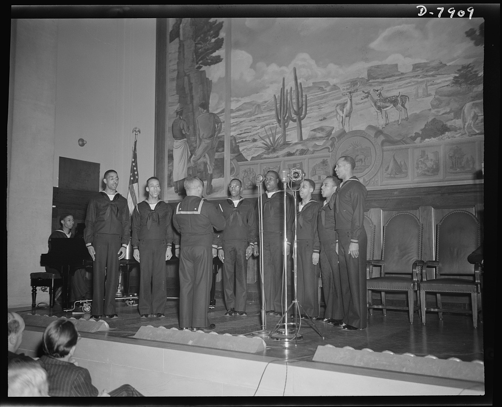 Marian Anderson mural dedicated. Musician (second class) Wayman E. Hathcock, directs a double quartet from Camp Robert Smalls, Great Lakes Training Station, at the dedication of a mural commemorating Marian Anderson's free public concert on the steps of the Lincoln Memorial on Easter Sunday, 1939. The dedication was held in the Department of Interior Auditorium before a distinguished audience on January 6, 1943