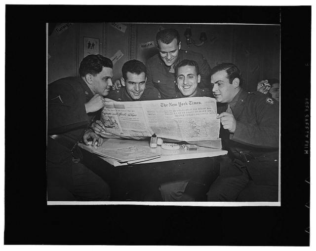 Men from New York State crowding around an out-dated copy of a New York newspaper at an American Red Cross club somewhere in England. Left to right: Private First Class Ted Rothstein, Bronx; Private Gene Binchoni, Bronx; Sergeant T. David Bernstein, Brooklyn; Private Jack Perino, Bronx, and Private Harold Plovsky, Manhattan