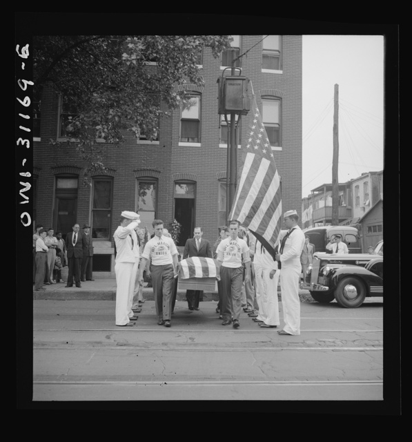 Merchant marine seaman given military funeral. Bearing the casket of Herman Sweitzer, one of the members of the merchant marine who lost his life in the recent ammunition ship-tanker collision off Norfolk. National Maritime Union men march through a Coast Guard color guard as they leave the Sweitzer home, 501 North Monroe Street, Baltimore. This was the first time a military funeral was held for a member of the merchant marine