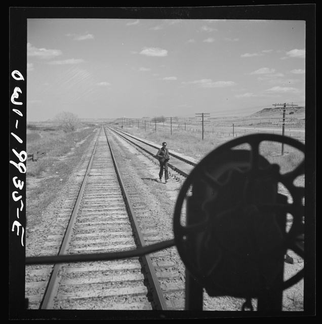 Miami, Texas. On the Atchison, Topeka and Santa Fe Railroad between Canadian, Texas and Amarillo, Texas. Rear brakeman running back to train as it gets ready to start again after having taken water