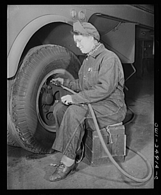 Milwaukee, Wisconsin. War production workers at the Heil Company making gasoline trailer tanks for the U.S. Army Air Corps. Mrs. Angeline Kwint, age forty-five, an ex-housewife, checking the tires of trailers. Her husband and son are in the U.S. Army