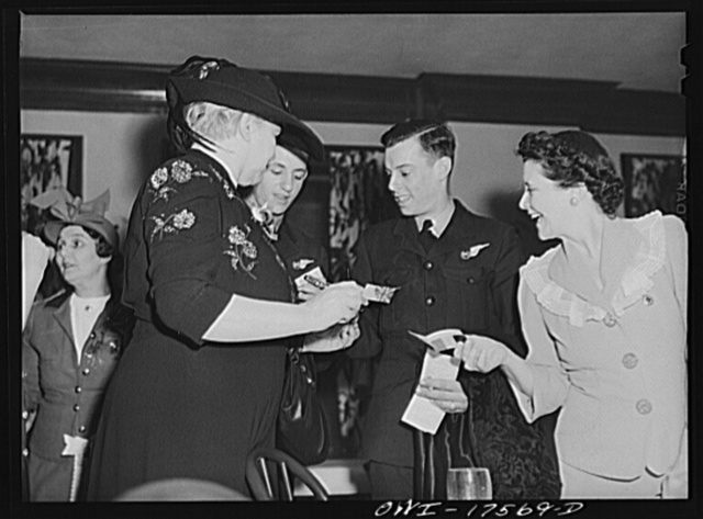 Minneapolis, Minnesota. Sister Kenny signing autographs at an American Legion meeting at which she was the principal speaker. With her (in uniform) are Sergeant C.N. Macqueen, from Sidney, and Sergeant J. Rutherford, from Brisbane, both of the Australian Air Force