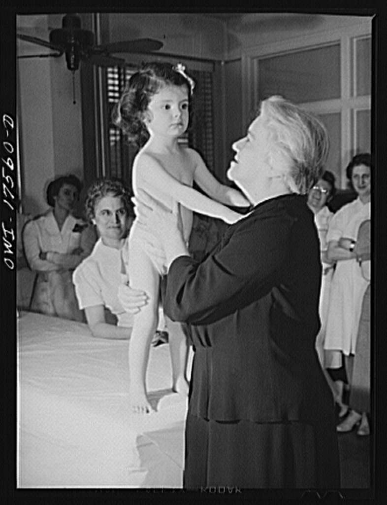 Minneapolis, Minnesota. Sister Kenny with two-year-old Winifred Gorman, a patient at the Kenny Institute. Winifred was admitted in November, 1942, a very serious case, stricken with infantile paralysis in both legs, spine and abdomen. She can now walk and use her arms freely. She is almost completely recovered, and will be discharged in a few weeks