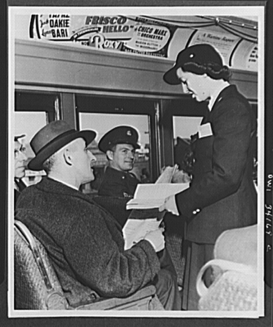 Miss Mildred L. Bunel, Long Island Railroad woman trainmen consulting a timetable for a passenger