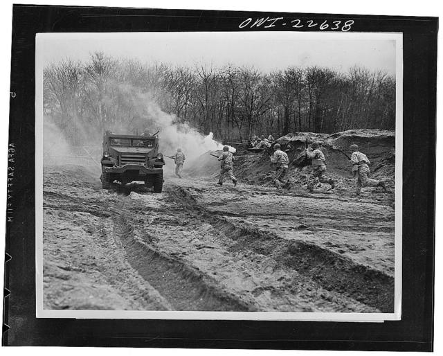 Mitchel Field, Long Island, New York. Camouflaged troops repel attack on half track carrying an x-ray portable field unit in a simulated battle test. The unit is set up in battlefront areas in a specially constructed dark-room tent