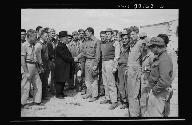Monsignor Spellman shaking hands with Corporal George T. Robinson while touring the Tunisia front. When Archbishop Francis J. Spellman handed a diploma to Robinson at the Fordham University commencement in New York City in 1937, neither had the remotest idea that they would meet again at a United States Air Force fighter base in Tunisia