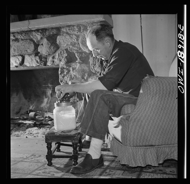 Moreno Valley, Colfax County, New Mexico. William Heck, a stockman, churning butter after a hard day in the saddle