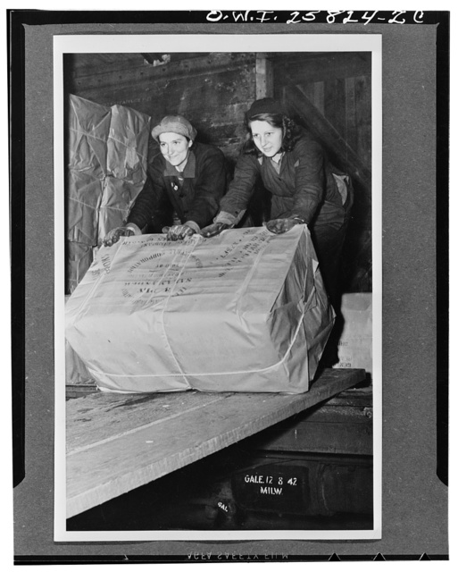 Mrs. Esther Henderson (left), of Lyons Station, and Mrs. Orville Sloyer, unloading bales of insulating material for storage in the lumber shed