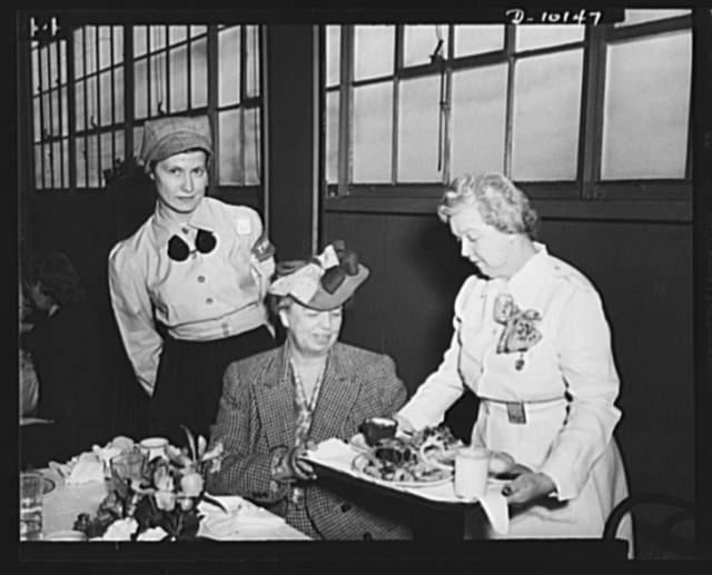 Mrs. Roosevelt is served a Victory lunch on her visit to General Motors' Eastern Aircraft Division in Linden, New Jersey. Consisting of a small steak, two vegetables, salad, enriched breads, custard and a glass of milk, this highly nutritious lunch is provided war workers for forty-seven cents in the plant cafeteria. Mrs. Clairs C. Curthrie, plant nutritionist, hands Mrs. Roosevelt the tray, while welder-trainee Emmie Banys stands by