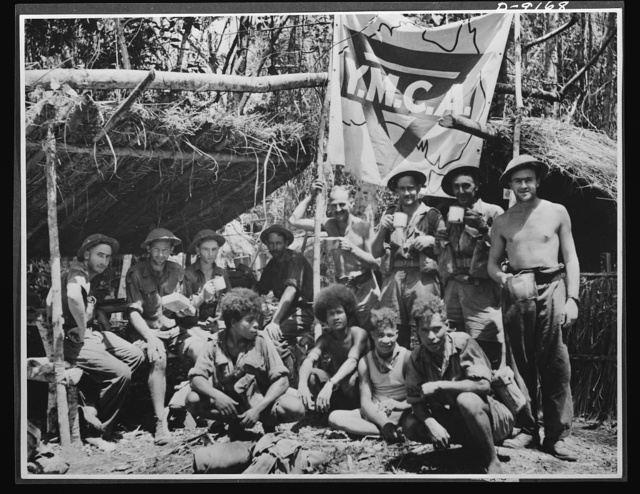 Natives aid Allied drive in New Guinea jungles. A short rest period in the New Guinea campaign. Natives and Allied troops pause at a YMCA (Young Men's Christian Association) unit in a forward area. These natives give invaluable aid to the Allied forces in transporting supplies and wounded soldiers through trackless jungles
