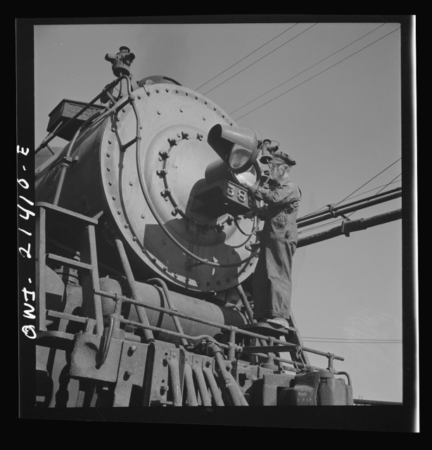 Needles, California. Electrician B. Fitzgerald cleaning the headlight of a locomotive at the Atchison, Topeka, and Santa Fe Railroad. All engines operating west of Needles are equipped with hooded headlights in accordance with the blackout regulations