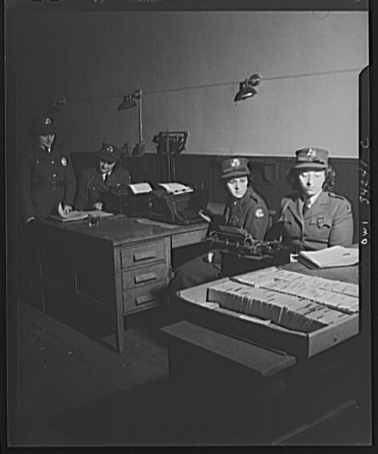 New Britain, Connecticut. New Britian auxiliary policewomen checking and writing out reports on their patrol duties