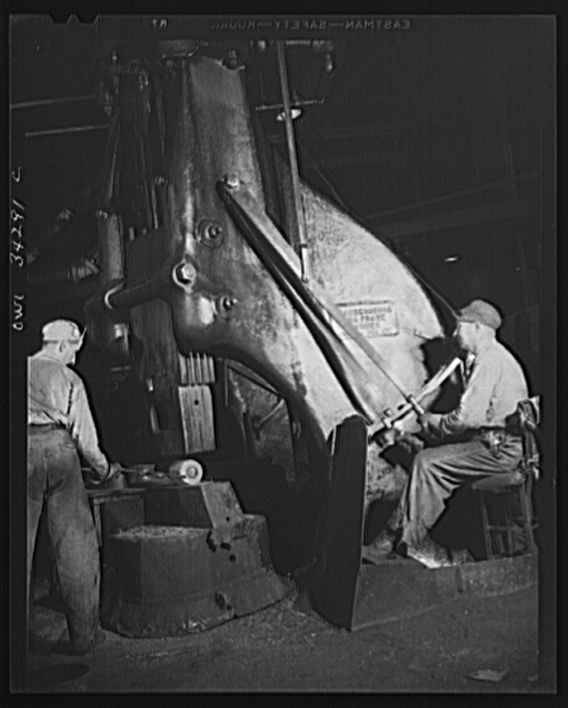 New Britain, Connecticut. Peter Juliana, steam-hammer operator and Bidwell Hughes, steam-hammersmith, working with a Chamers-ring steam hammer at the Fafnir Bearing Company