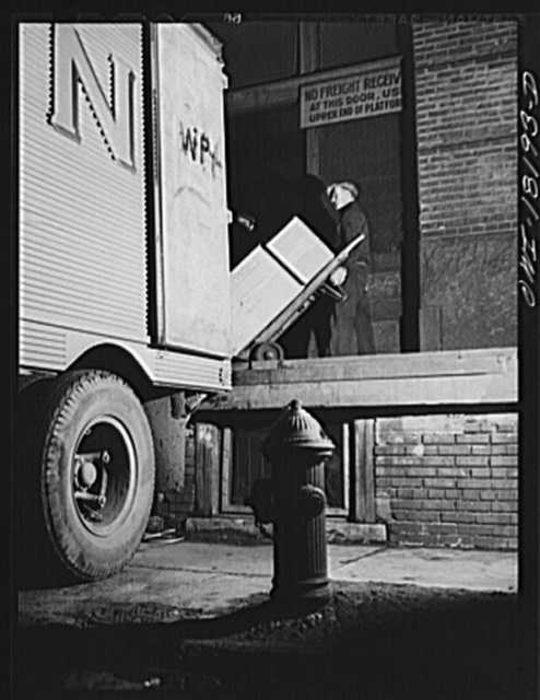 New York, New York. Associated Transport Company trucking terminal on Washington Street. Loading goods on a southbound transport truck