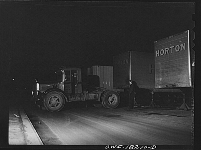 New York, New York. Associated Transport Company trucking terminal on Washington Street. Backing a tractor to a loaded trailer which is going south