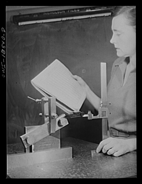 New York, New York. Class in the use of precision instruments, part of the government-sponsored industrial training program at New York University. Most of the students are women. Testing the angle of a machined part in degrees and minutes with a five-inch sine bar and vernier height gauge, and consulting a table of constants for a five-inch sine bar