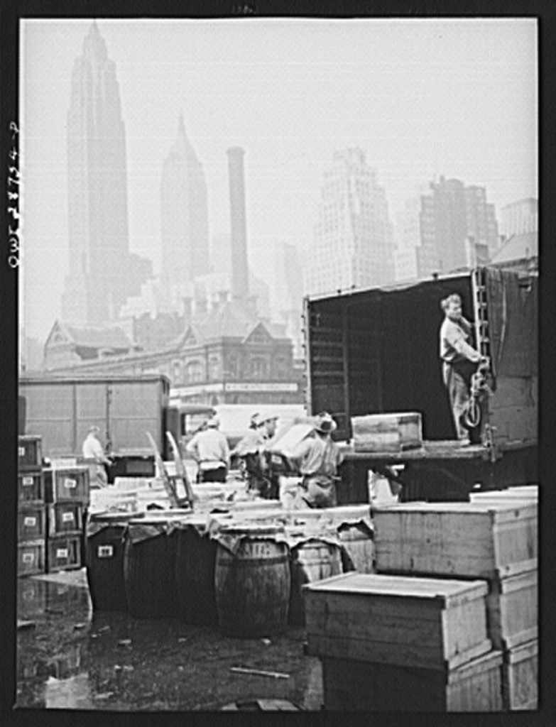 New York, New York. Dock workers loading boxes of fish onto trucks for shipping to retailers