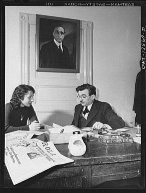 New York, New York. Girolamo Valente, editor of the progressive Italian weekly, La Parola, conferring with his secratary. The ashtray in the form of open-mouthed Mussolini was presented by a friend. Painting on the wall is of Giacomo Matteotti, an Italian patriot. Valente is a prominent anti-fascist in this country