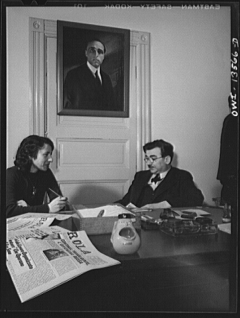 New York, New York. Girolamo Valente, editor of the progressive Italian weekly, La Parola, conferring with his secretary. The ashtray in the form of open-mouthed Mussolini was presented by a friend. Painting on the wall is of Giacomo Matteotti, an Italian patriot. Valente is a prominent anti-fascist in this country