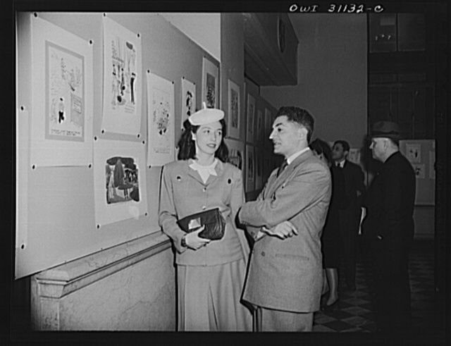 New York, New York. Margo Cooke, and Louis Priscilla, Chairman of the Committee on War Cartoons of the American Society of Magazine Cartoons, discussing their contribution to an exhibition of cartoons concerning lost hours in war production, sponsored by the OWI (Office of War Information)