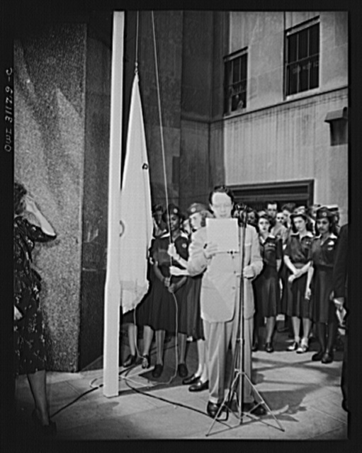 """New York, New York. Radio announcer reading the preamble of the """"Four Freedoms"""" while the flag is being raised, at the opening ceremonies at the Four Freedoms war bond show on the plaza of the International Building in Rockefeller Center"""