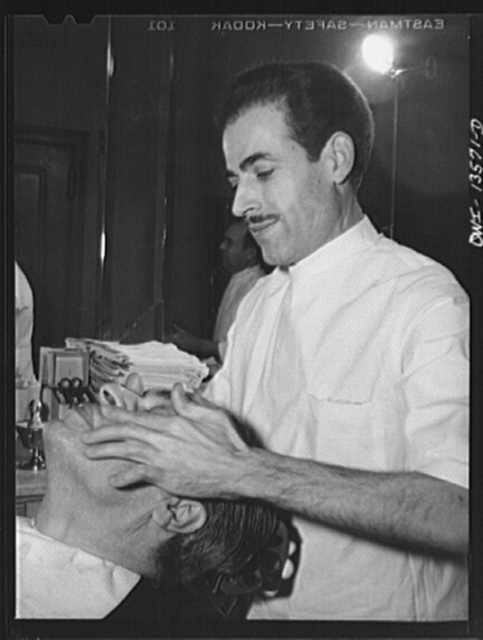 New York, New York. Vincent giving a face massage in his barber shop on West Eighth Street