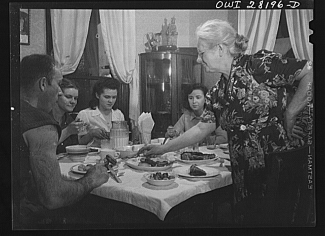 Niagara Falls, New York. War workers who live at Mrs. Hannegan's boardinghouse having supper at 5:30