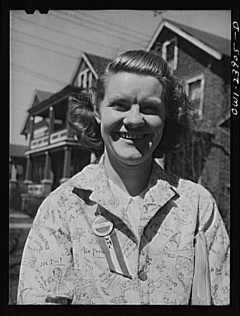 Niagra Falls, New York. Nan Hannegan doing door to door recruiting for women to work in war plants. This program was organized by the War Manpower Commission in cooperation with local war plants who loaned nineteen women workers. Nan wears a War Manpower Commission ribbon pinned on with her plant button