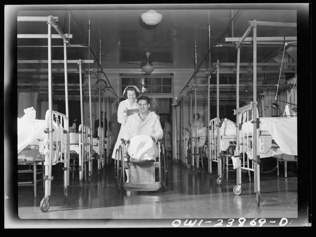 Nurse Frances Bullock wheels a wounded soldier back to his bed in the orthropedics ward of an Army hospital